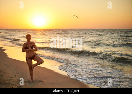 Authentic woman in swimsuit doing yoga vrikshasana on the beach in the morning. Real unretouched shape girl silhouette in tree pose asana near sea on - Stock Photo