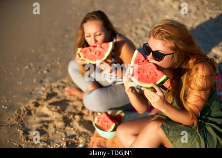 Girlfriends laughing and eating fresh watermelon at seaside in the morning. Two happy women friends sitting on towel and having a picnic on tropical - Stock Photo