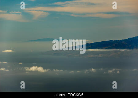 La Gomera and El Hierro islands, flying in the air between different clouds. Bright blue sky. View from 1900m of altitude. Teide National Park, Teneri - Stock Photo
