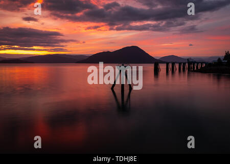 A stunning sunset across the flat calm waters just off the coast of Wrangell, Alaska, the sky full of beautiful pinks, reds and oranges - Stock Photo