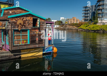 Victoria, Vancouver Island, British Columbia, Canada, July, 8, 2018: The floating homes in Victoria against a backdrop of a modern apartment block. - Stock Photo