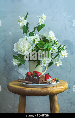 Chocolate roll cake with fresh strawberries, jasmine and white peonies in cup on wooden table. Artistic Still Life in the style of Dutch painting. Cop - Stock Photo