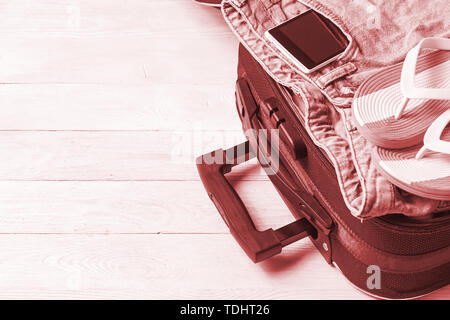 Open suitcase with travel accessories on white wooden table with copyspace. - Stock Photo