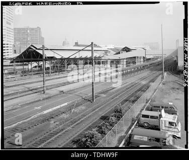 OVERALL VIEW, FROM SOUTH, OF MULBERRY STREET BRIDGE, SHOWING BOTH SHEDS, MAIL CONVEYOR CONNECTING POST OFFICE BUILDING TO LOADING DOCK UNDER WEST SHED (RIGHT SIDE), PLATFORM CANOPIES AND CATENARY SYSTEM. NOTE STATE CAPITOL DOME VISIBLE BEYOND STATION BUILDING - Pennsylvania Railroad, Harrisburg Station and Trainshed, Market and South Fourth Streets, Harrisburg, Dauphin County, PA - Stock Photo