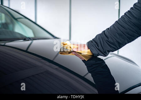 A person polishes the bonnet on his car with a leather cloth