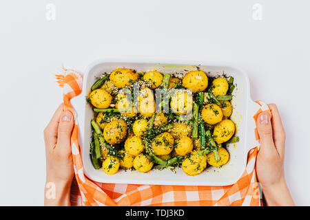 Woman's hands holding baking tray with freshly prepared homemade dish baked new potatoes with green beans on a white background, top view. - Stock Photo