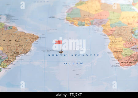 Small red flag marking the South Atlantic Ocean on a world map. - Stock Photo