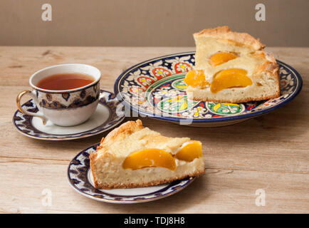 Slice of open peach apricot pie or cheese sour cream cake on bright saucer with tea cup on wooden table background macro close-up. - Stock Photo
