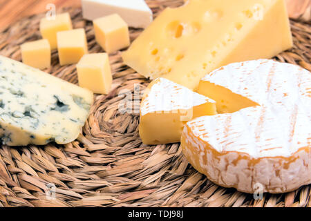 cheese of different types close-up on eco straw napkins - Stock Photo