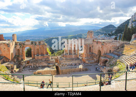 Taormina, Sicily, Italy - Apr 8th 2019: Beautiful ancient theatre of Taormina. Ancient Greek theatre, ruins of significant landmark. Amazing view of Etna volcano from the auditorium. - Stock Photo