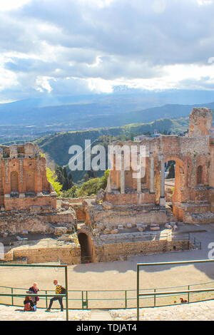 Taormina, Sicily, Italy - Apr 8th 2019: Amazing view from Ancient Greek theatre of Taormina. Ruins of historical landmark. Etna silhouette in the clouds in background. Popular tourist place. - Stock Photo