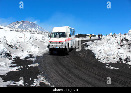 Etna, Sicily, Italy - Apr 9th 2019: Tourist jeep or bus driving tourists to the top of Etna volcano and back. Snow on the volcanic soil along the road. Very top in the background. - Stock Photo