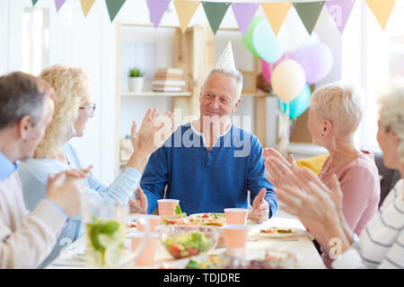 Group of excited friends sitting at dining table and applauding birthday man while congratulating him with celebration at dinner party - Stock Photo