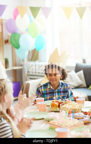 Portrait of smiling African-American boy wearing crown sitting at table while celebrating Birthday with friends - Stock Photo