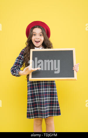 presenting product. small girl in french beret. happy girl with curly hair in beret. advertisement. child with empty blackboard. child on yellow. copy space. school time. presenting school project. - Stock Photo