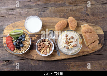 Top view of a healthy Breakfast of oatmeal, nuts, berries, milk and croissants. - Stock Photo