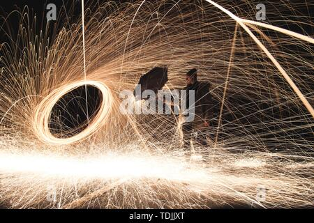 A man holding an umbrella close to a spinning sparking bright force circle field with sparks all around - Stock Photo