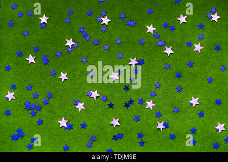 Blue and silver sparkles stars on a bright green background.  - Stock Photo