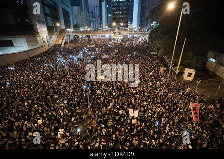 Protesters marched through the streets of Hong Kong during the mass rally, which called for, among other demands, the withdrawal of the controversial extradition bill and the resignation of Chief Executive Carrie Lam. Some used the lights on their phones to symbolize candles in order to respect to a person who fell from a scaffolding the day before after hanging an anti-extradition law banner. Despite the Chief Executive Carrie Lam's attempt to ease the heightened tension by agreeing to suspend the controversial bill, close to 2 million people participated in Sunday's rally, according to the o - Stock Photo