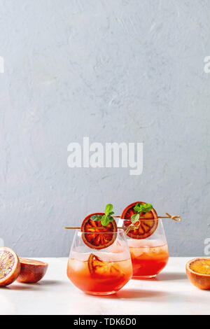 Blood orange iced cocktails in glasses, decorated by slice of oranges and fresh mint on skewers, served on white marble table with grey wall at backgr - Stock Photo