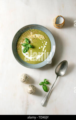 Green vegetable soup asparagus, broccoli or pea, decorated by basil, sesame seeds, cream in ceramic bowl with salt and pepper, jug of cream over white - Stock Photo