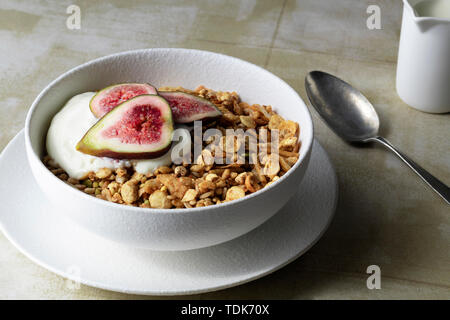Healthy breakfast of muesli, yoghurt and sliced figs. - Stock Photo