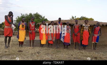 wide view of a group of ten maasai women and men singing from enkereri village near maasai mara game reserve in kenya - Stock Photo
