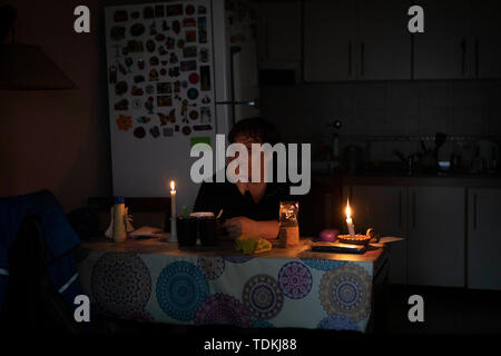 Buenos Aires, Argentina. 16th June, 2019. A citizen lights candles during a blackout in Buenos Aires, Argentina, June 16, 2019. The massive blackout occured in Argentina at about 7:00 am local time (1000 GMT) and also hit Uruguay, southern Brazil and multiple cities in Chile. Credit: Martin Zabala/Xinhua/Alamy Live News - Stock Photo