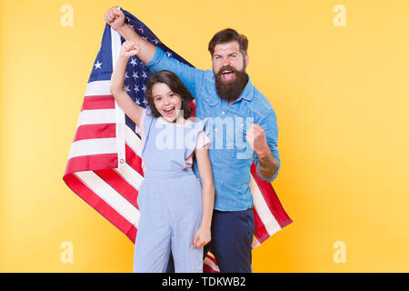 Getting in the holiday spirit. Father and small child holding american flag on national holiday. Happy family celebrating annual 4th of july holiday. Independence day is federal holiday in the usa. - Stock Photo