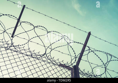 barbed wire steel wall against immigations. Wall with barbed wire on the border of 2 countries. Private or closed military zone against the background - Stock Photo