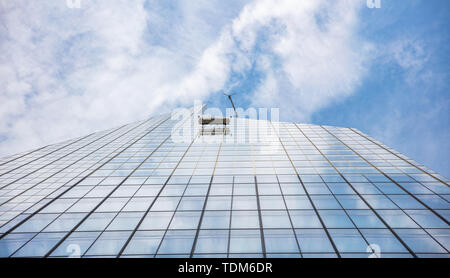 New York, Manhattan. Glass window cleaning services, glass facade skyscraper against blue sky background, low angle view, - Stock Photo