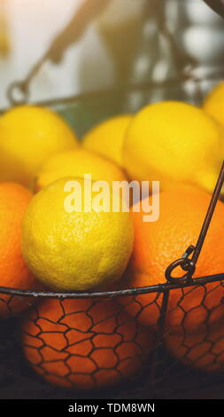 Oranges and Lemons in basket on bar counter - Stock Photo