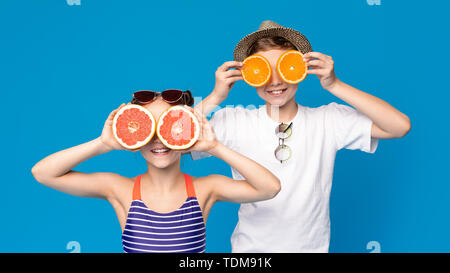 Cheerful girl and boy wearing citrus eyeglasses - Stock Photo