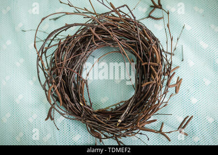 Wreath woven from tree branches. Handmade blank for crafts made of wood. Children make a wreath of branches, nest for birds - Stock Photo