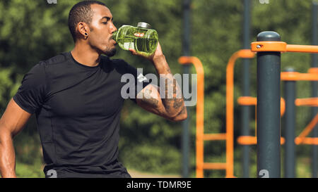 Sporty Man Drinking Water After Workout Outdoors