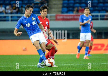 English-born Taiwanese football player Tim Chow, left, of Henan Jianye passes the ball against a player of Tianjin Tianhai in their 13th round match during the 2019 Chinese Football Association Super League (CSL) in Tianjin, China, 16 June 2019.  Tianjin Tianhai played draw to Henan Jianye 1-1. - Stock Photo