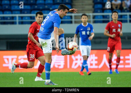 English-born Taiwanese football player Tim Chow, right, of Henan Jianye passes the ball against a player of Tianjin Tianhai in their 13th round match during the 2019 Chinese Football Association Super League (CSL) in Tianjin, China, 16 June 2019.  Tianjin Tianhai played draw to Henan Jianye 1-1. - Stock Photo
