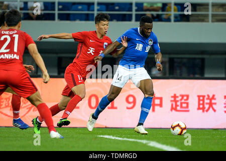 Cameroonian football player Franck Ohandza, right, of Henan Jianye passes the ball against a player of Tianjin Tianhai in their 13th round match during the 2019 Chinese Football Association Super League (CSL) in Tianjin, China, 16 June 2019.  Tianjin Tianhai played draw to Henan Jianye 1-1. - Stock Photo
