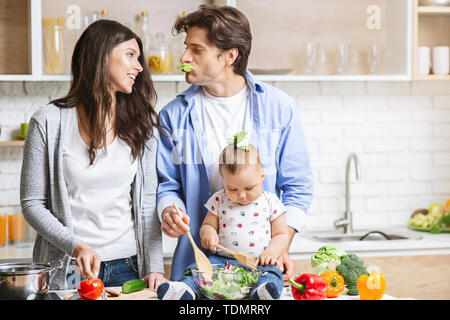 Photo of young loving couple parents with their little baby son cooking in kitchen. - Stock Photo