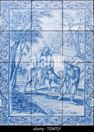 CATANIA, ITALY - APRIL 8, 2018: The ceramic tiled Flight to Egypt scene on the facade of Curia Arcivescovile by F. Fodinlio from 20. cent. - Stock Photo