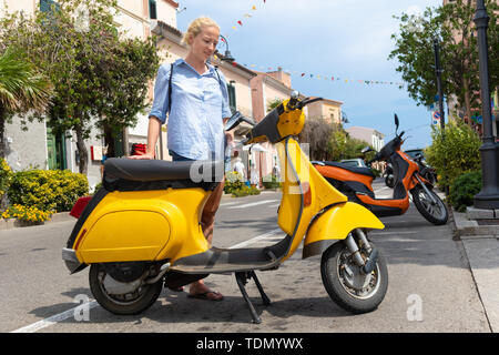 Young Female tourist wearing backpack bag parking traditional italian yellow vintage urban retro scooter on the street of Palau, Sardinia, Italy. - Stock Photo