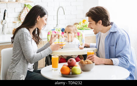 Good looking young family eating breakfast together with their baby - Stock Photo