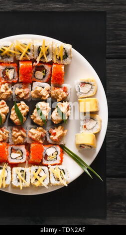 Set of sushi for two with chopsticks on rustic wood background - Stock Photo