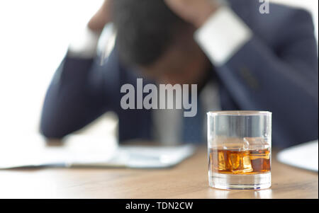 Desperate african business suffering at workplace with glass of whiskey - Stock Photo