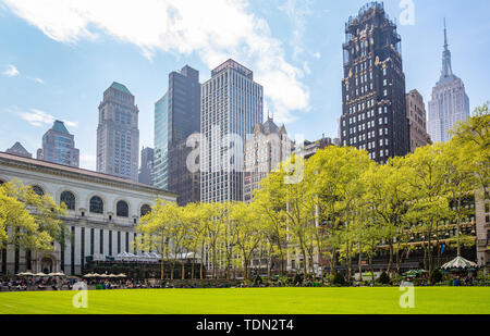 New York, Manhattan, Skyline view from Bryant park, springtime. Skyscrapers, people relaxing, green lawn and trees, clear blue sky background - Stock Photo