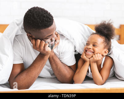 Cute african dad and daughter lying on bed and smiling to each other Stock Photo