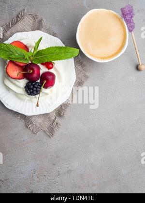 Pavlova meringue cake with fresh berries on white plate, coffee latte - Stock Photo