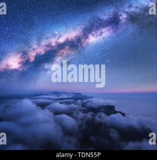 Milky Way over the low clouds and sea coast at starry night - Stock Photo