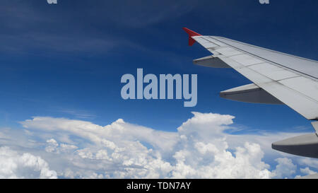 airplane flight. wing of an airplane flying above the white clouds and blue sky. beautiful aerial view from the window of the plane on travelling time - Stock Photo