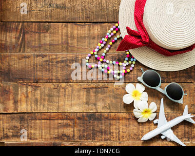flat lay of hat , necklace , sun glass , flower and red heart shape as traveler's accessories items for summer vacation and plane model on wooden back - Stock Photo